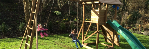 2 kids playing on a climbing frame